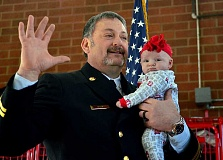 REVIEW PHOTO: VERN UYETAKE - With granddaughter Riley looking on, newly promoted Battallion Chief Troy Bany is sworn in during a ceremony Saturday at the Lake Oswego Fire Department's downtown fire station.