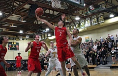 TIDINGS PHOTO: MILES VANCE - Lincoln's Bryce Sloan stretches for a reverse layup during his team's 76-65 loss at West Linn in the second round of the Class 6A state playoffs on Friday.