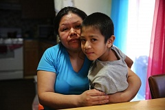 (Image is Clickable Link) COURTESY PHOTO: AMELIA TEMPLETON/OPB - Rosalina Guzman sits with her youngest son. She and her husband, Roman, have five children who were born in the United States and are citizens.