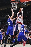 TRIBUNE PHOTO: JOSH KULLA - The Philadelphia 76ers try to stop Blazers center Jusuf Nurkic during Thursday's game at Moda Center.