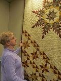 PHOTO BY ELLEN SPITALERI - Shirley Workman, chairman of the quilt show committee, points out the intricate quilting on 'Startacular,' the raffle quilt for this years quilt show, on March 17 and 18 at the Milwaukie Center.