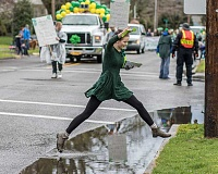 NEWS-TIMES PHOTO: CHASE ALLGOOD - A Murphy's Furniture volunteer leaps a puddle while passing out fliers during Saturdays annual St. Patricks Day Parade in Hillsboro.