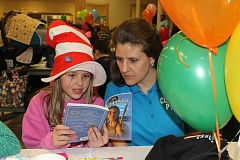 SUBMITTED PHOTO - Micaela and Debby Taylor read a book at Culver Elementary's 20th Green Eggs and Ham Dinner. Every child received a free book.