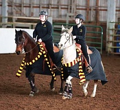 PHOTO CREDIT: STAINAKERS PHOTOGRAPHY - Lions junior Chasity Cuthair, left, on her horse, Whiskey, and junior Courtney Rasczewski, right, on Chant, perform a Harry Potter-themed routine in the working pairs event at the second Oregon High School Equestrian Teams Northwest District meet at the Yamhill County Fairgrounds in McMinnville.