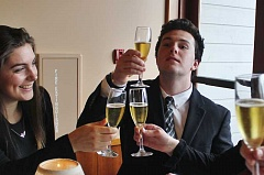REVIEW PHOTO: KELSEY OHALLORAN - Sam Haney (center) raises a (nonalcoholic) toast to his tablemates, including Rowen Anderson (left), at an Etiquette Dinner histed by the National League of Young Men on Sunday.