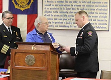 SUBMITTED PHOTO - American Legion Post Commander Bob Gnos presents Lt. Chad Carey (right) with a plaque honoring him as Hillsboro Firefighter of the Year as Fire Chief Scott Magers looks on.