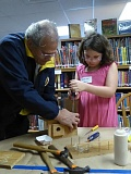 COURTESY PHOTO - Volunteer Lowell Bauer helps Addison Wells with the construction of her birdhouse on Saturday, March 11. Volunteers from the library helped create basic templates for the children to follow using seven pieces of wood. The children helped on every step, while the volunteers helped the children with the more technical parts of the birdhouse construction.