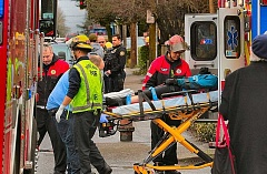 DAVID F. ASHTON - A Portland Fire & Rescue lieutenant checks in with the victim, who is conscious as hes being loaded into a waiting ambulance.