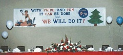 "KIWANIS PAST GOVERNORS COMMITTEE - The banner on the wall over a past Governor's Convention shows the slogan that Molalla Kiwanians say epitomizes John Chelson: ""With Pride and Fun, it can be done, and We Will Do It."""