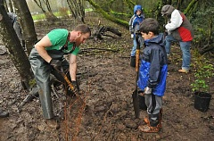 SPOKESMAN PHOTO: VERN UYETAKE - Waylon Burlingame and his son Waylon work hard to remove some roots to clear the ground for a new tree during the pollinator habitat planting in Wilsonville March 18.