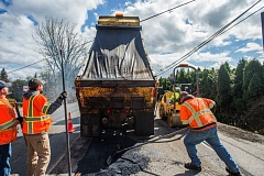 OUTLOOK PHOTO: JOSH KULLA - Gresham Public Works employees Bruce Lucky, Jeremy Turin and Kary Moore fill potholes on Southeast Orient Drive during a recent rare sunny day.