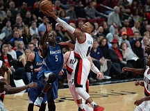 TRIBUNE PHOTO: JOSH KULLA - Damian Lillard of the Trail Blazers slips to the basket against Minnesota as Portland wins at Moda Center on Saturday night.