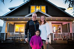 PAMPLIN MEDIA GROUP: ADAM WICKHAM - Kevin and Amanda Bates stand outside Symposium Coffee Sherwood along with their daughter with their 7-year-old daughter Nittaya, a second-grader at Hopkins Elementary School. The couple opened the shop in 2011 and purchased the 1911 American Craftsman-style bungalow house in 2015.