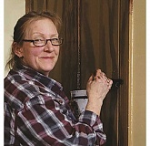 IRIS RILEY - Local artist Victoria Knight at work putting a new finish on old woodwork in Molalla's Dibble House museum.