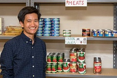 NEWS-TIMES PHOTO: CHRISTOPHER OERTELL - Jared Kawatani stands next to shelves of food that he has collected to help Pacific University students in need.